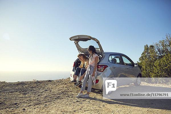Südafrika  Kapstadt  Signal Hill  zwei junge Frauen bei einem Auto an der Küste