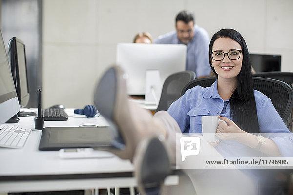 Büroangestellte entspannt am Arbeitsplatz bei Kaffee