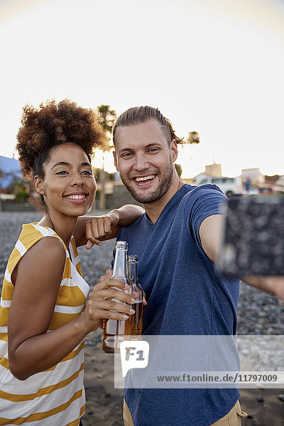 Zwei Freunde mit Bierflaschen  die Selfie am Strand mitnehmen.