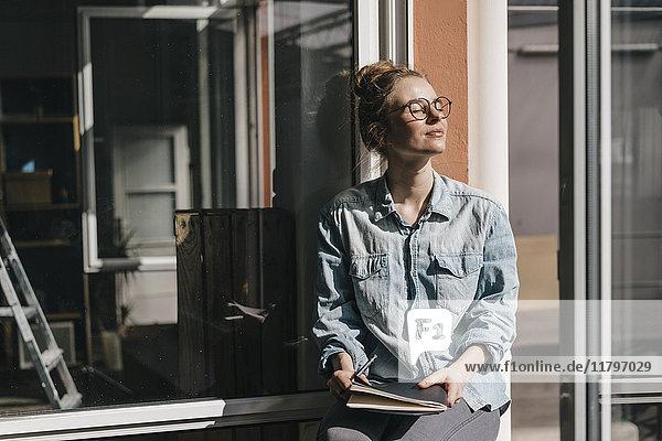 Junge Frau mit Brille im Sonnenlicht
