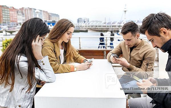 Gruppe von Freunden  die ihre Smartphones benutzen