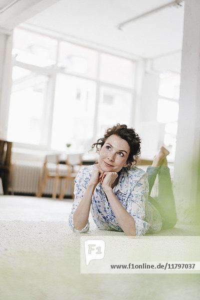 Eine Frau  die in ihrer Wohnung auf dem Boden liegt und denkt.