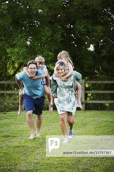 Mann und Frau rennen über einen Rasen  tragen Junge und Mädchen huckepack  eine Familie im Freien.