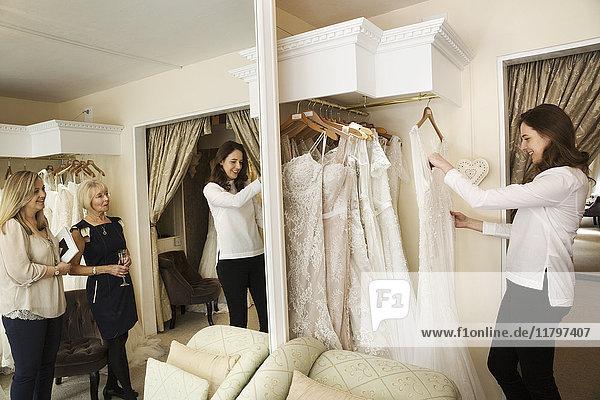 Drei Frauen  eine Kundin und zwei Einzelhandelsberaterinnen in einem Brautkleidergeschäft  die die Auswahl der Kleider durchsehen. Großer Spiegel und Reihen von Brautkleidern.