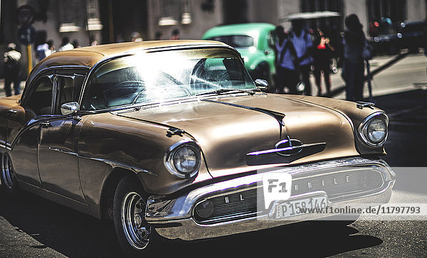 A classic 1950s car in a busy street.