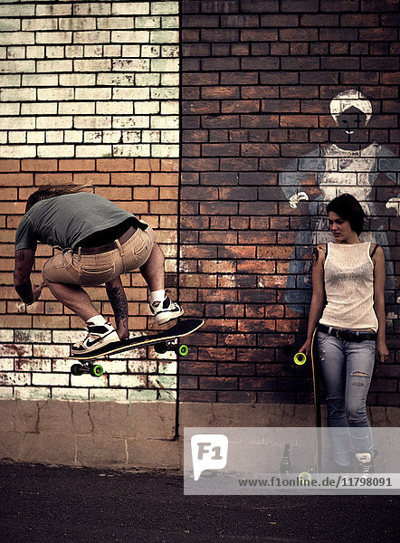A young man and woman skateboarding in front of a brick wall.