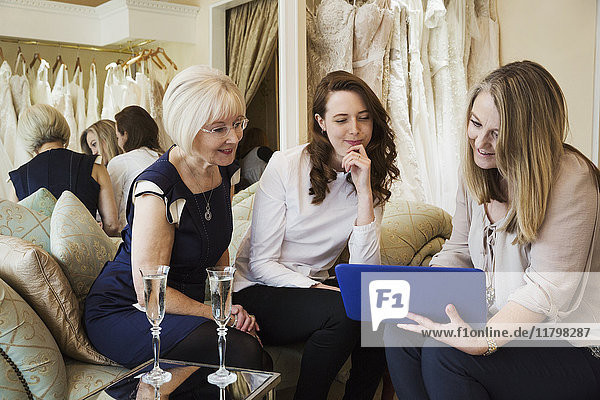 Three women in a wedding dress shop  one bride to be and two retail advisors looking at a digital tablet. Two glasses of champagne on the table.