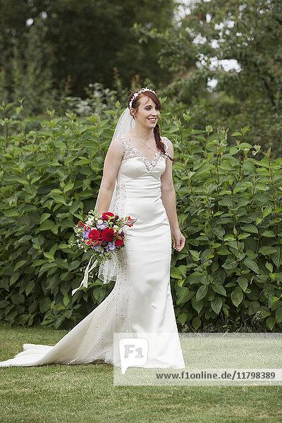 Braut in ihrem Brautkleid steht in einem Garten und hält einen Brautstrauß aus roten Blumen.