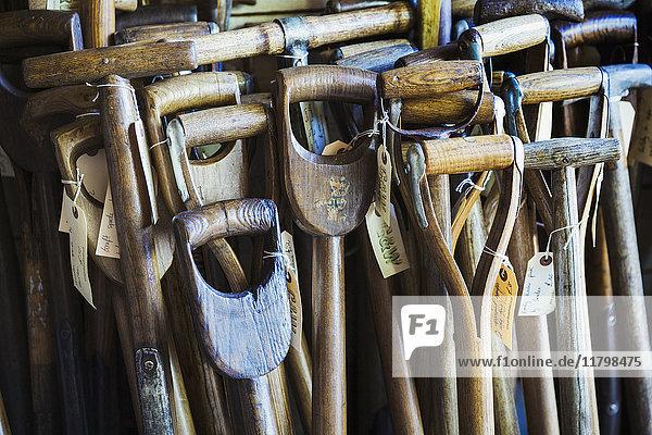 Nahaufnahme der abgenutzten und verwitterten Holzgriffe alter traditioneller Spaten in einer Werkstatt mit angebrachten Informationsetiketten. Nahaufnahme der abgenutzten und verwitterten Holzgriffe alter traditioneller Spaten in einer Werkstatt mit angebrachten Informationsetiketten.