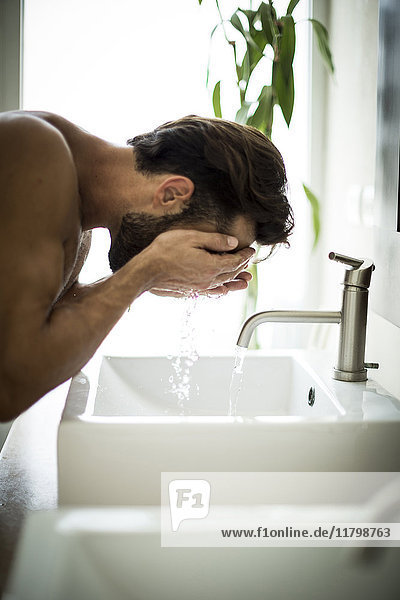 A man standing at a sink washing his face.