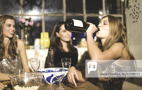 A group of friends around a table at a party  one girl drinking from a bottle of champagne.