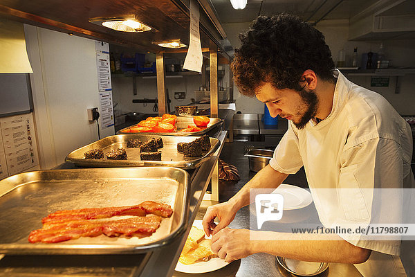 Chef standing in a restaurant kitchen at a counter plating food  trays with bacon  Black Pudding and grilled tomatoes.