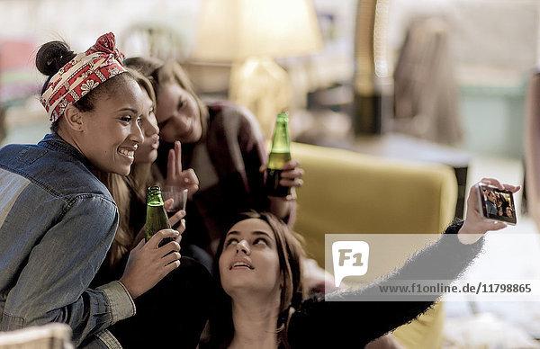 Vier junge Frauen sitzen lachend auf einem Sofa  nehmen einen Selfie und halten Bierflaschen in der Hand.