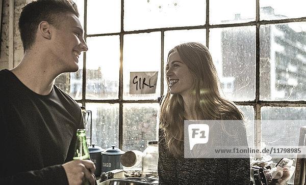 Lächelnde junge Frau und junger Mann halten eine Bierflasche in der Hand und stehen drinnen am Fenster.