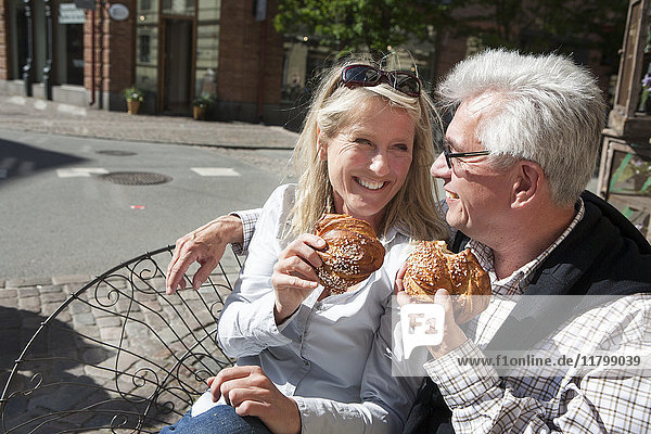 Mature couple eating croissants in sidewalk cafe
