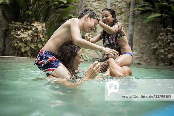 Zwei Kinder auf den Schultern von Erwachsenen spielen in einem Schwimmbecken Kämpfe.