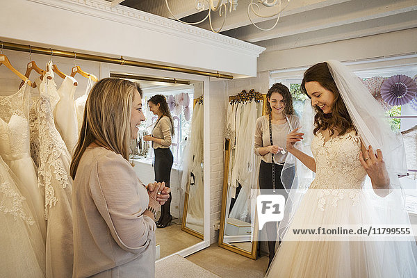 A bride trying on a dress  with the assistance of two women in a bridal boutique.