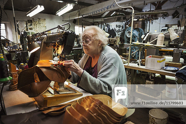 Older woman sitting at a sewing machine in a shoemaker's workshop.