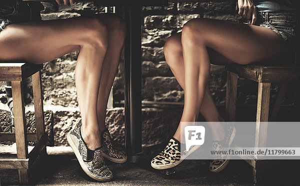 Shot of the legs of two young women under a small table.