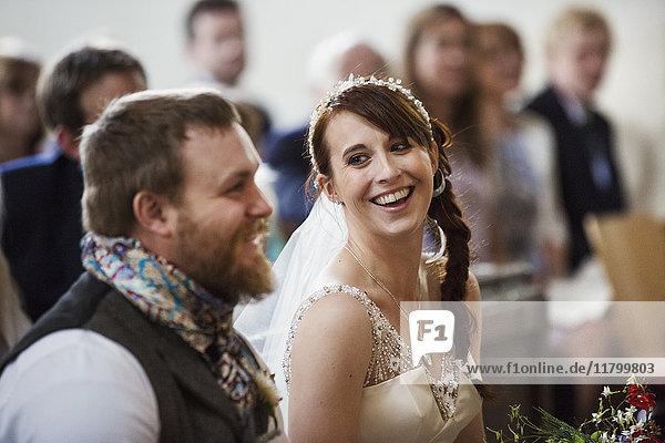 Lächelnde Braut und Bräutigam bei ihrer kirchlichen Trauung.