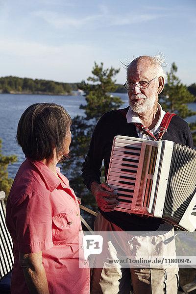 Senior man playing accordion to senior woman