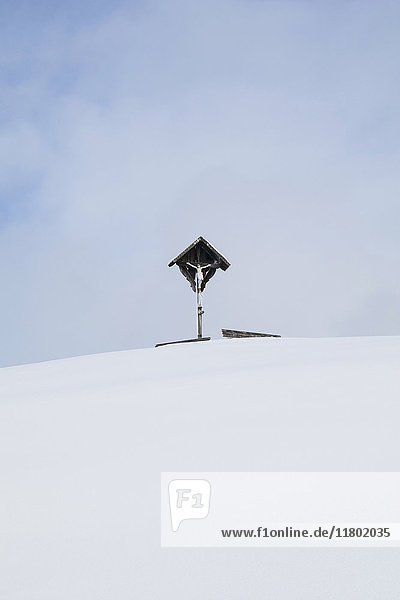 Crucifix on snowcapped mountain against sky with cloud