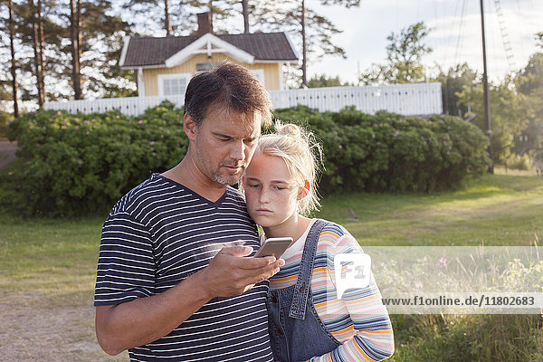 Father with daughter looking at cell phone