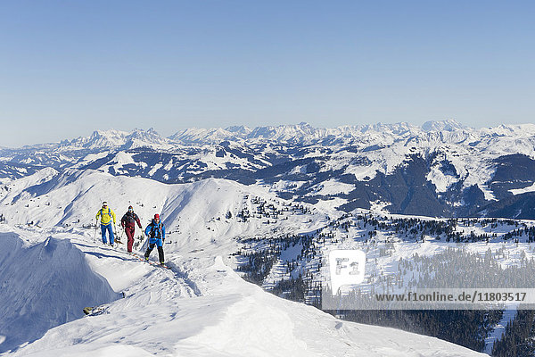 Skiers walking on ridge of snow mountain