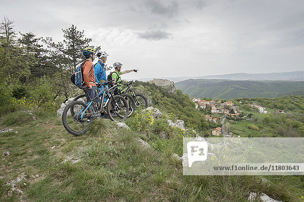 Three mountain bikers standing on rocky mountain and looking at distance