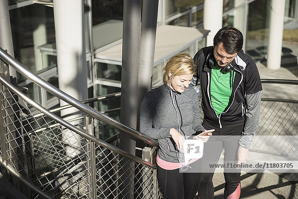 Man and woman in sportswear using smart phone with headphones