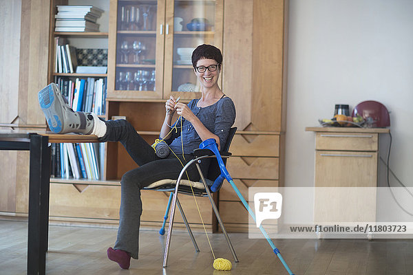 Woman resting broken leg on table and knitting at home
