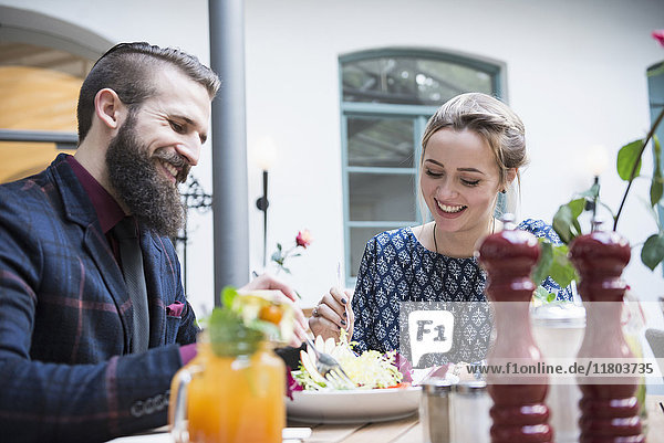 Cheerful couple eating salad at restaurant