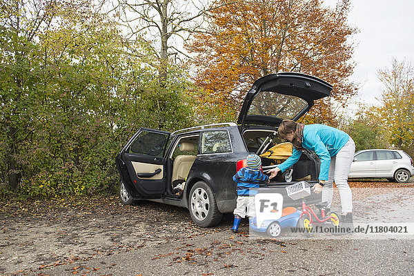 Mother and son packing walking wheel out of the boot of a car in an autumn scenery