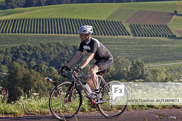 Mountain biker riding on road by green field