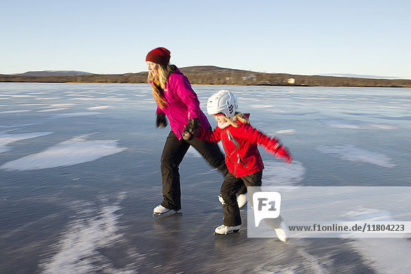 Mother and daughter ice-skating on frozen lake