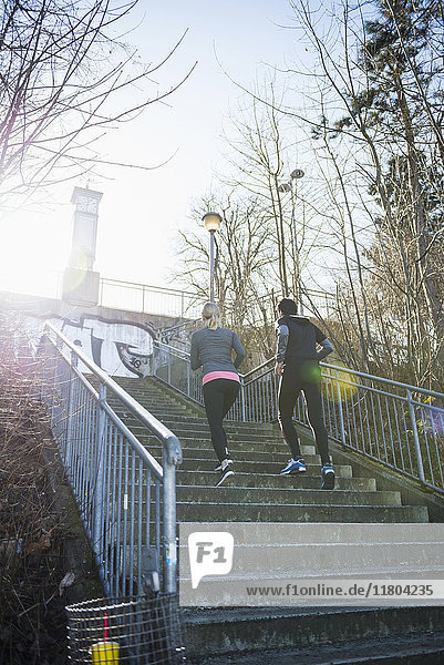 Man and woman jogging up stairs