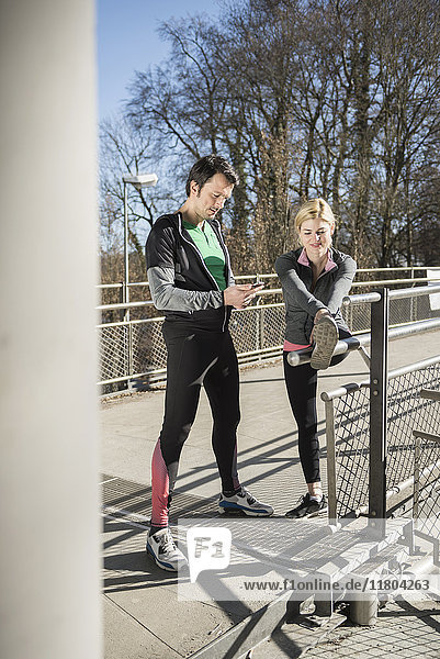 Man checking smart phone while woman is stretching outdoors
