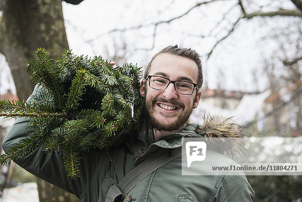 Portrait of young man carrying Christmas tree