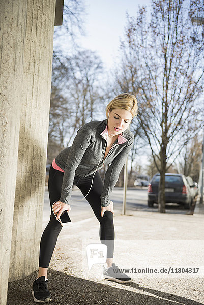 Woman listening music on smart phone and taking a break from workout
