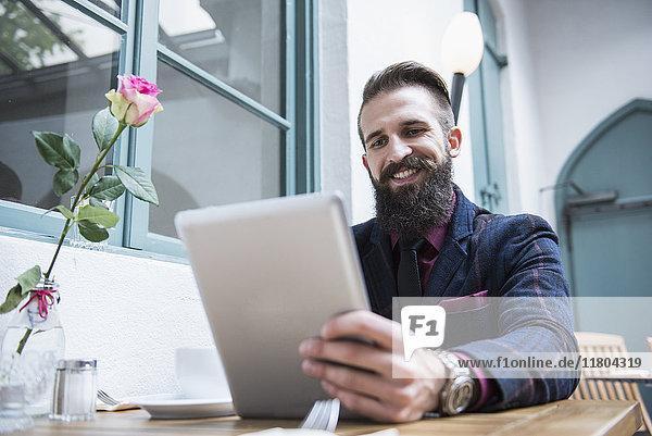 Smart businessman using digital tablet while sitting at café
