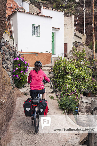 Woman riding electric bicycle towards buildings in village