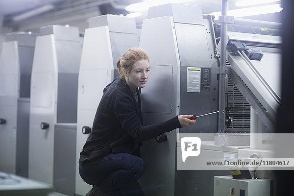 Female worker repairing multiple printing machinery