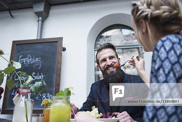 Woman feeding food to man at restaurant