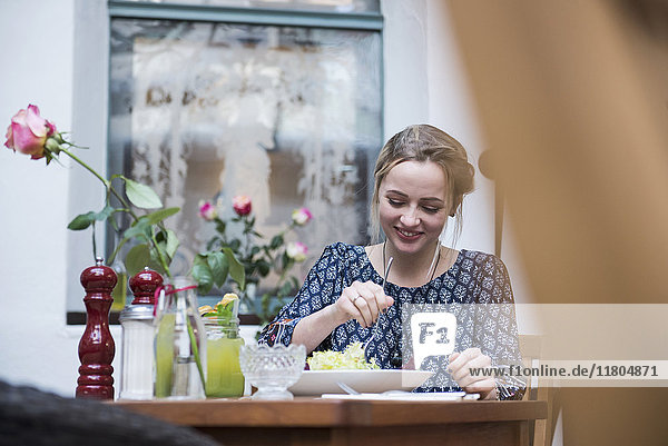 Young woman eating salad at restaurant