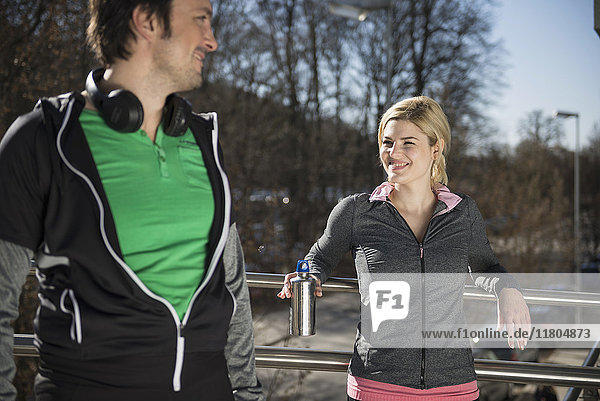 Man and woman in sportswear relaxing after workout