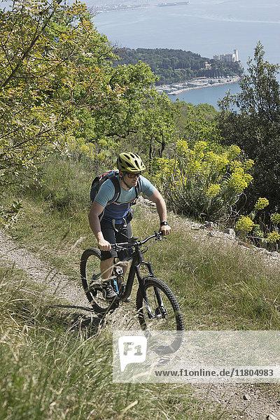 Mature biker riding bike on trails through dirt road