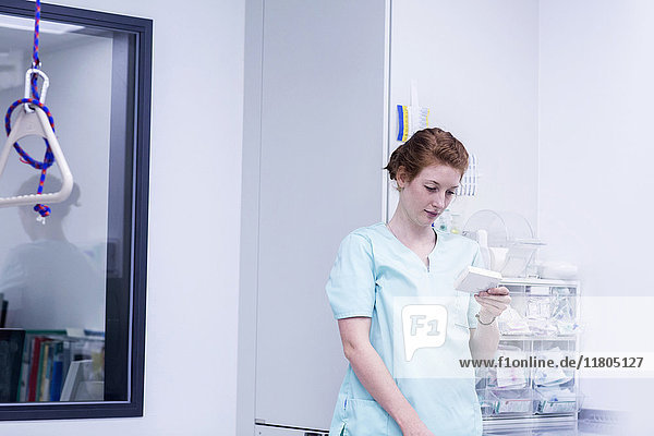 Nurse holding medicine while standing in store room at hospital