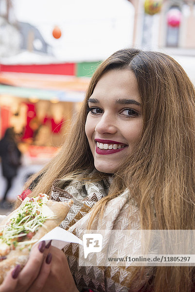 Portrait of young woman eating at Christmas market