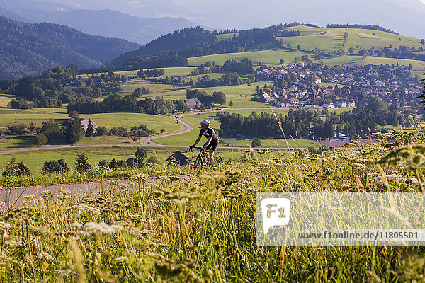 Mountain biker riding on road amidst green field