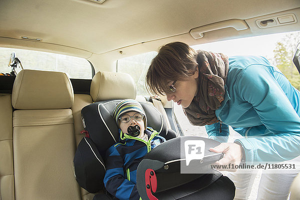 Mother clipping on the seat belt of her son with pacifier in his mouth sitting in child seat in car